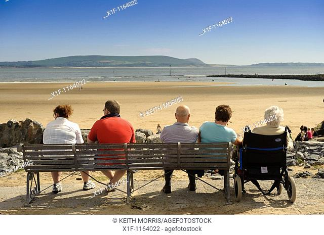 People sitting on a seaside bench at The Millennium Coastal park, Burryport, Carmarthenshire South Wales UK