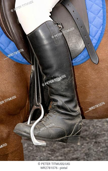 Riding boot positioned into a bent leg safety stirrup used in horse riding