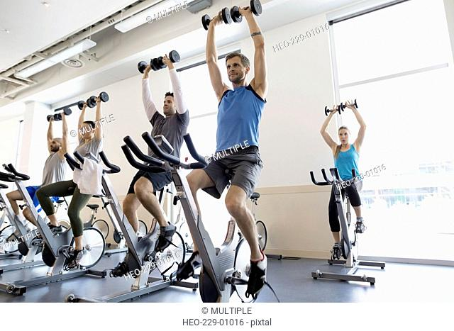 Spin class holding barbells overhead stationary bikes gym
