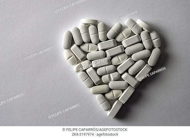 White pills in the shape of heart isolated on white fund, conceptual image