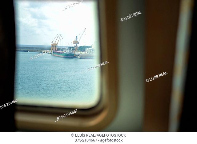 View from the cabin window of a ship of a dock with a cargo ship at the Port of Palma de Mallorca, Balearics, Spain