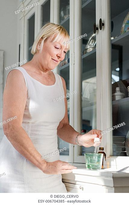 Health issues and people, mature woman with prescription medicine and glass of water