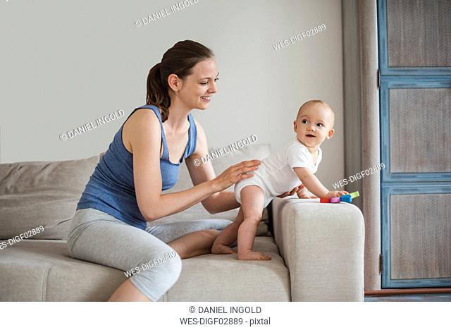 Happy baby girl with mother playing on couch