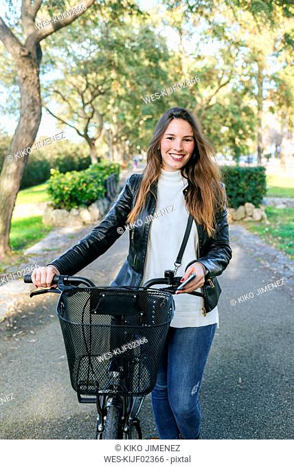 Portrait of smiling young woman with bicycle in park