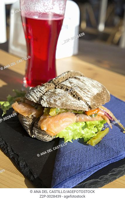 Salmon sandwich with red beer on table