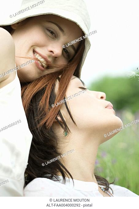 Two female friends outdoors, one leaning against the other