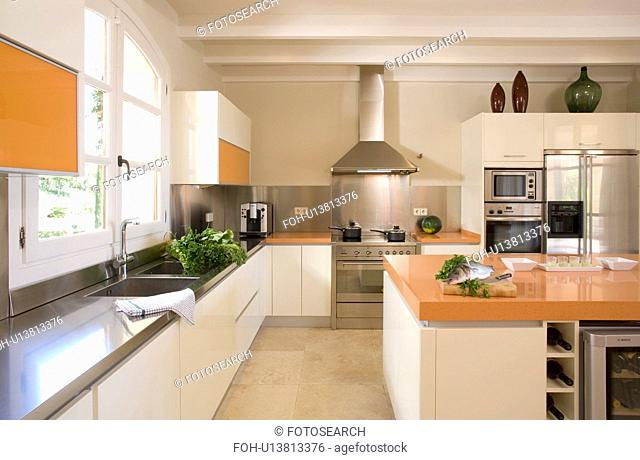 Stainless steel and white kitchen with large island unit for food preparation
