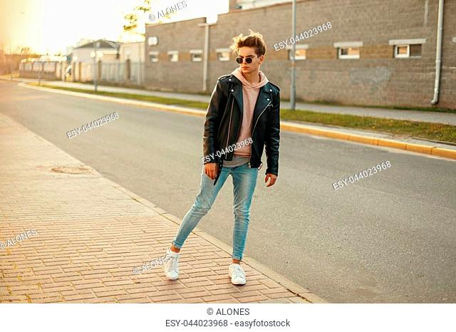 Young model guy in a black leather jacket, a pink sweatshirt, jeans and white sneakers posing on the street