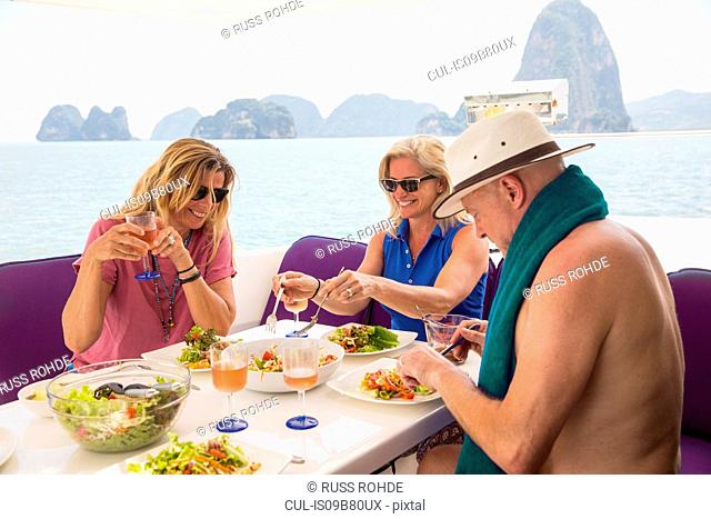 Friends having lunch on yacht, Koh Hong, Thailand, Asia