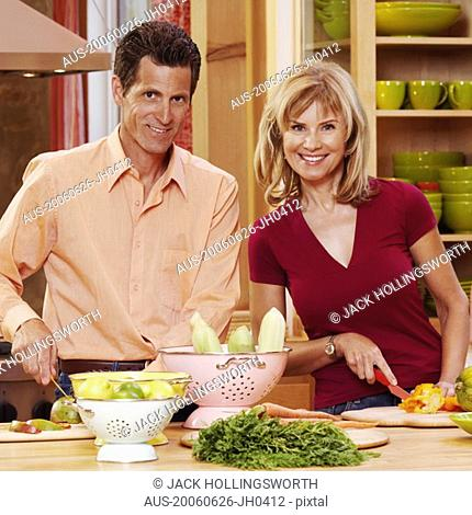 Portrait of a mature couple cutting vegetables and smiling
