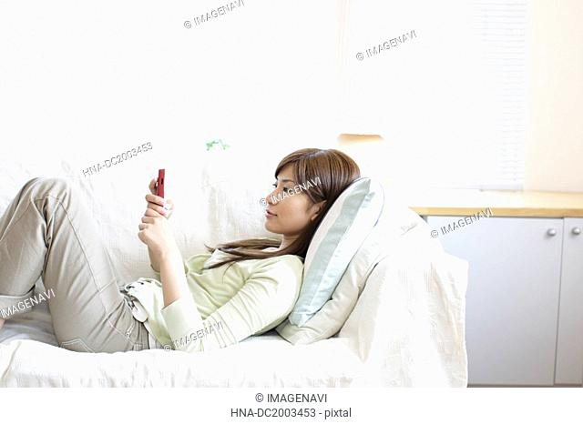 Woman Lying on a Sofa Holding a Cell-Phone
