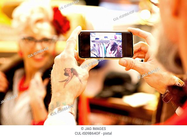 Tattooed hands of senior man taking smartphone photo of girlfriend in antique and vintage emporium