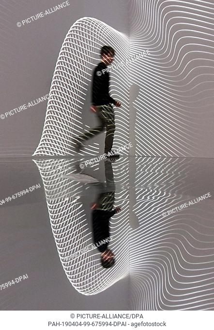 """03 April 2019, Baden-Wrttemberg, Karlsruhe: At the Center for Art and Media (ZKM), a person walks through Refik Anadol's installation """"""""Infinity Room"""""""" from..."""