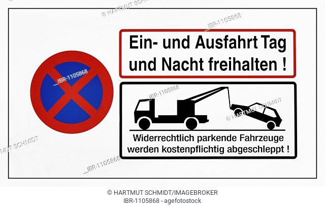 Instruction sign with parking prohibition symbol, tow truck and German text saying driveway must be kept clear day and night! unlawfully parked vehicles will be...