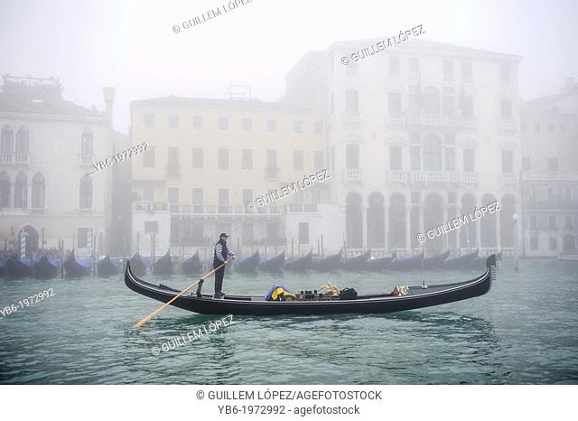 A Gondola sails along the Grand canal of Venice covered with thick fog, Italy