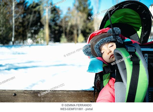 France, Osseja, cute baby girl sleeping in a kid carrier backpack on a bench in a snowy park