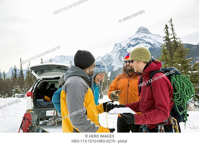 Group of friends looking at map in mountains
