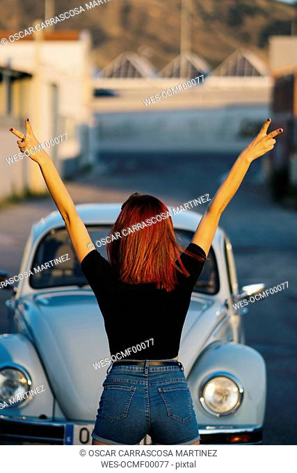 Redheaded woman standing infront of vintage car making victory sign, rear view