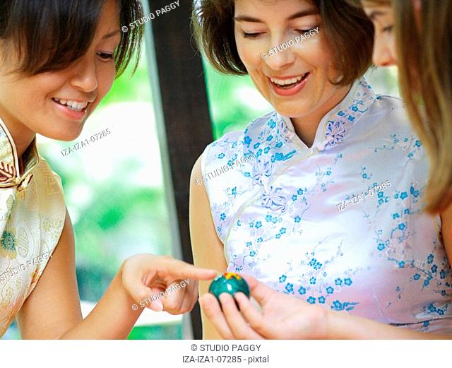 Close-up of a teenage girl and two women looking at a yin yang ball and smiling