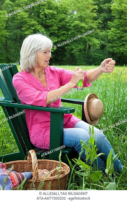 Elderly lady spraying on bug repellant