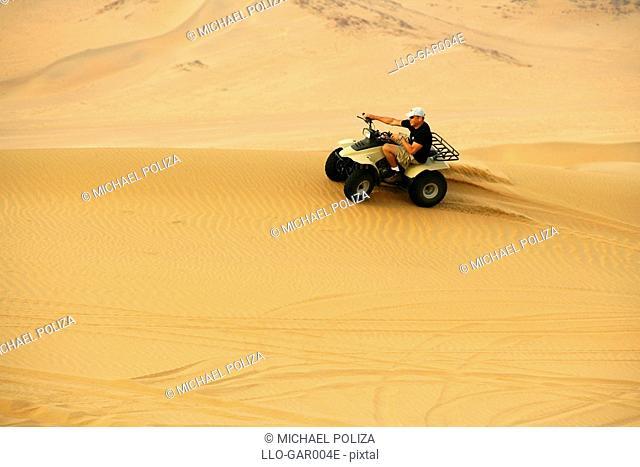 Man on a Quadbike on a Desert Dune  Namib Desert, Namibia