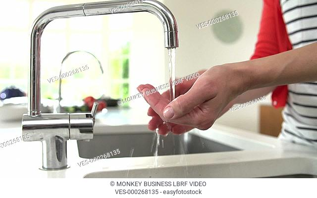Close up of woman washing hands under tap in kitchen.Shot on Sony FS700 in PAL format at a frame rate of 25fps