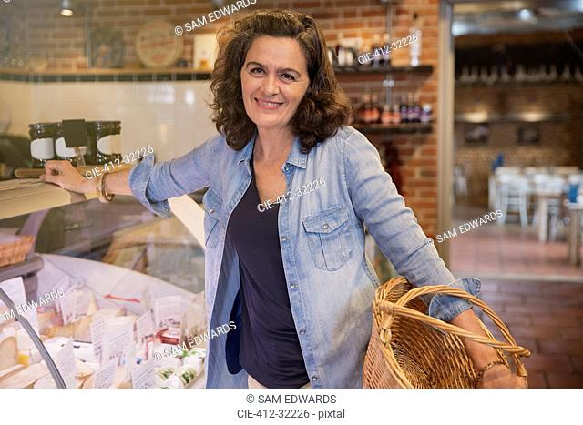 Portrait smiling woman with basket leaning on cheese display case in market