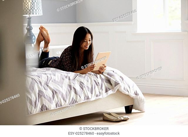 Woman Relaxing On Bed Using Digital Tablet