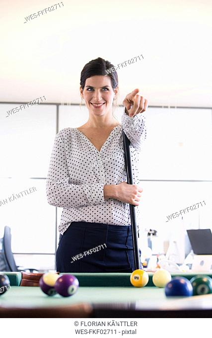 Businesswoman standing at pool table, playing billard, pointing