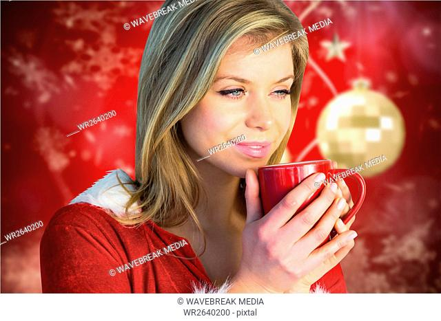 Beautiful woman having a cup of coffee during christmas time