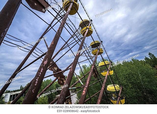 Yellow gondolas of ferris wheel in amusement park, Pripyat ghost city of Chernobyl Nuclear Power Plant Zone of Alienation in Ukraine
