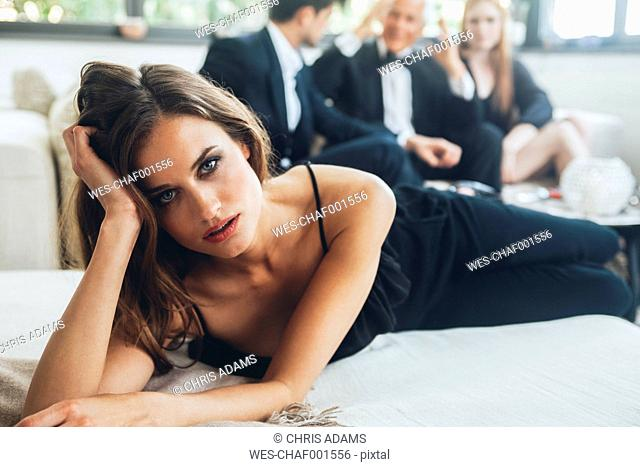 Beautiful woman lying on couch, party guests in background