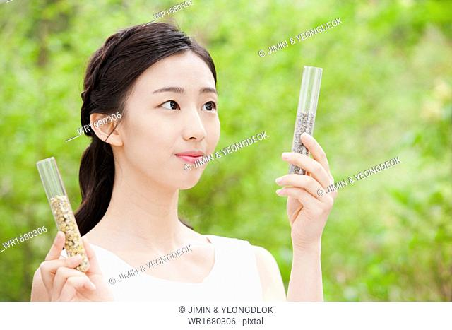 a woman holding two cosmetic bottles in the nature