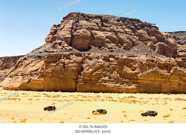 Three Vehicles driving past Wadi Teshuinat, Akakus, Sahara desert, Fezzan, Libya