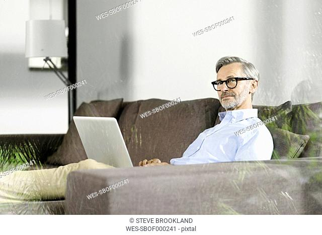 Man sitting on couch in his living room with laptop
