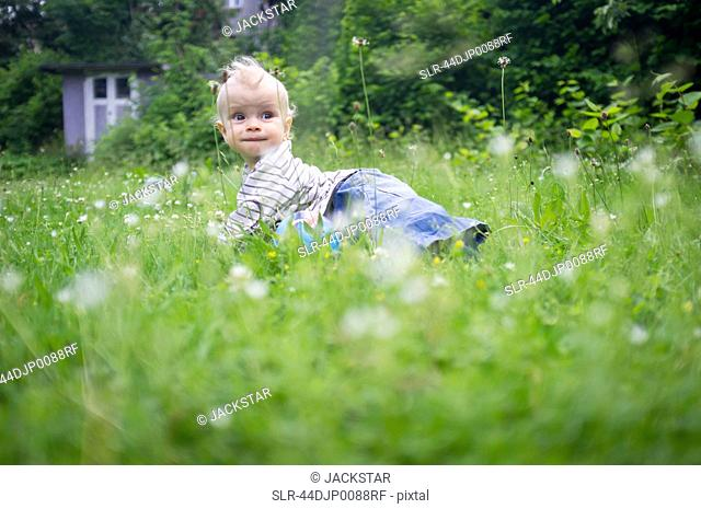 Baby girl crawling in tall grass