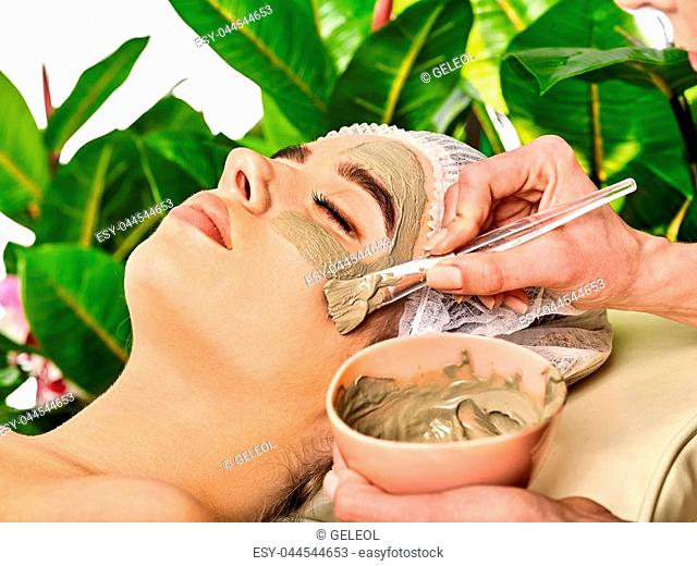 Mud facial mask of woman in spa salon. Massage with clay full face in therapy room. Removing wrinkles. Applying beautician with bowl therapeutic procedure on...