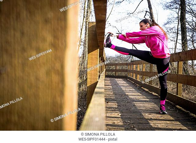 Woman stretching on wooden bridge in forest