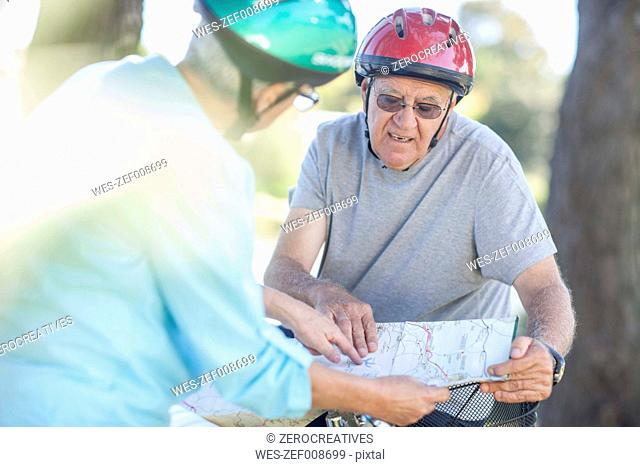 Elderly couple with map on bicycles