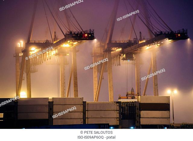 Misty view of harbor cranes and stacked cargo containers at night, Seattle, Washington, USA