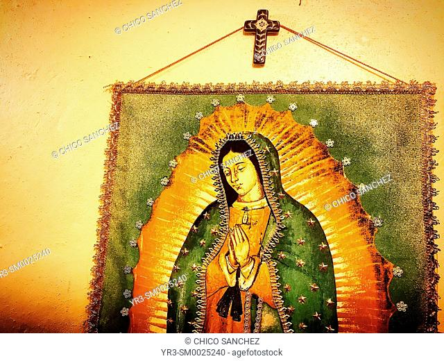 An image of Our Lady of Guadalupe and a cross decorate a house in Coyoacan, Mexico City, Mexico