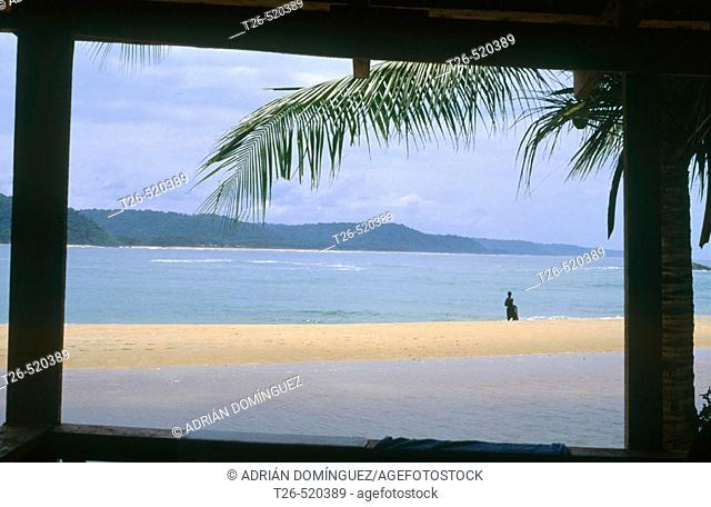 Window looking to the beach from a cabin in Monogaga river beach. Fisherman on the shore. Ivory Coast