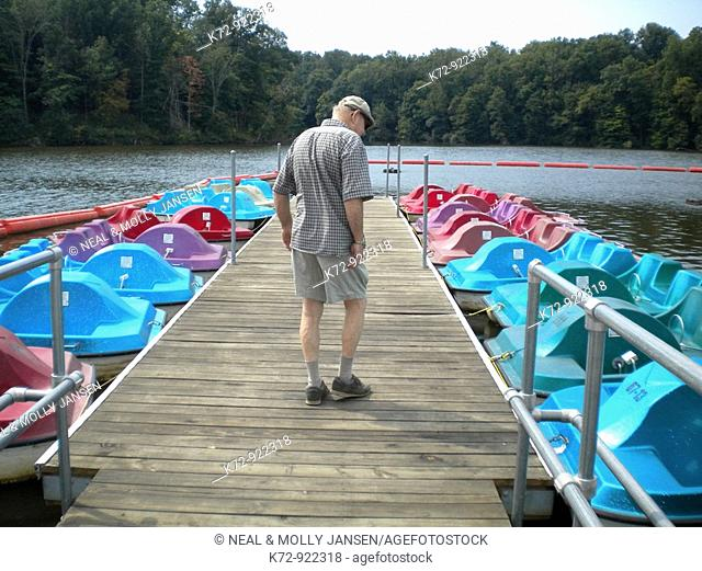 Man looking at recreational rental boats in park on lake