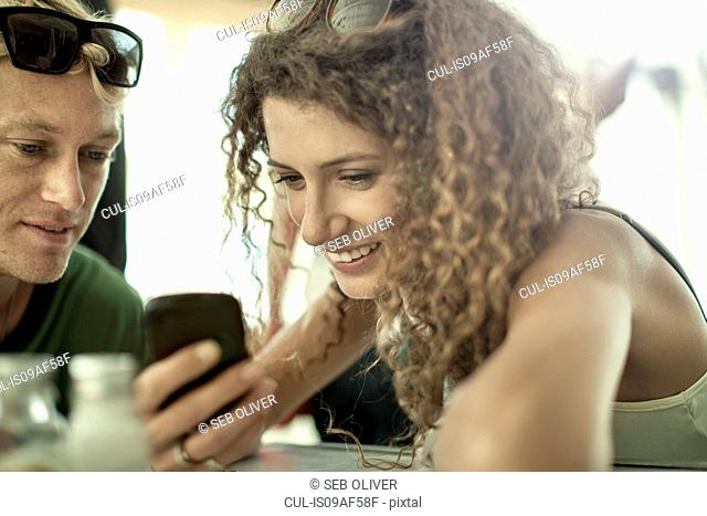 Young couple looking at cellphone in cafe bar