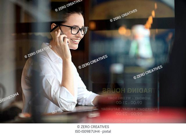 Woman in coffee shop using smartphone smiling