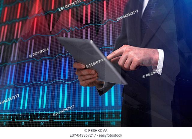 Businessman using tablet on abstract background with forex chart and building. Double exposure