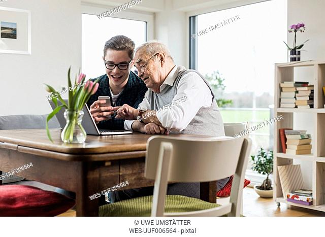 Senior man and his grandson sitting at table in the living room with laptop and smartphone