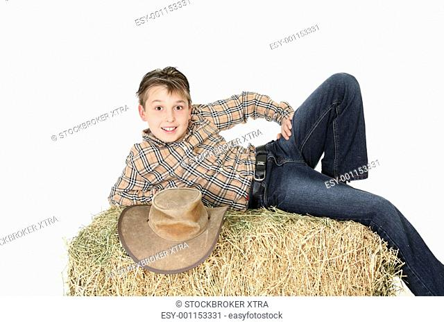 Rural child from the country lying on hay bale