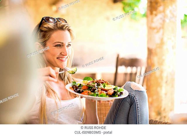 Young woman relaxing on garden patio eating salad