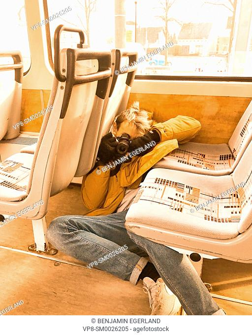 models view of playful photographer laying on floor between seats in city tram, public transport, taking photographs, in Cottbus, Germany